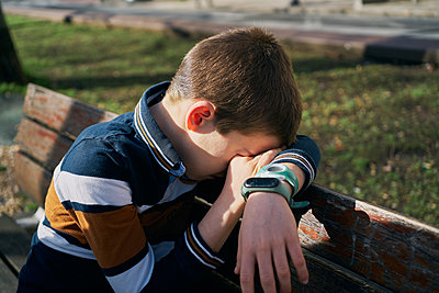 child on a bench covers his face with his arm and is crying - p1166m2193874 by Cavan Images