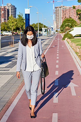 Woman walking down the street with a mask. - p1166m2218313 by Cavan Images
