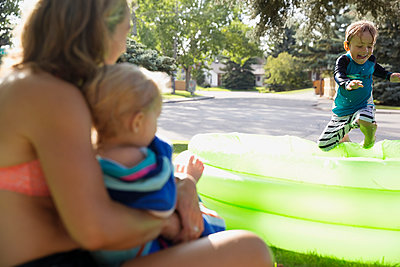 Mother and daughter watching playful son jumping into sunny wading pool - p1192m1184007 by Hero Images