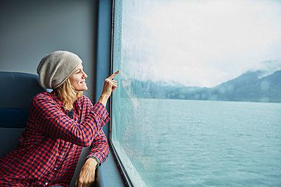Chile, Hornopiren, woman drawing a heart on the window of a ferry - p300m2069188 by Stefan Schütz