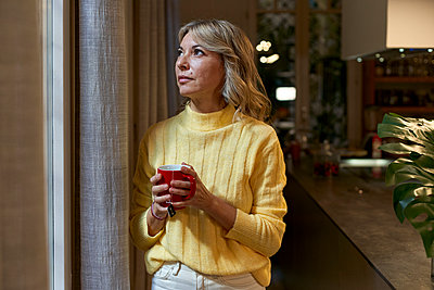 Fashionable mature woman looking through window while holding tea cup in kitchen - p300m2241794 by Veam