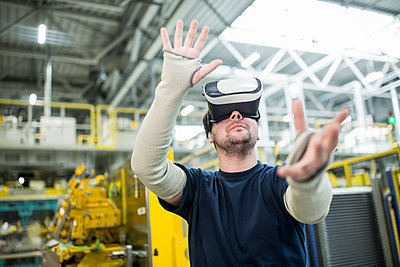 Man wearing VR glasses in modern factory - p300m2246023 by Westend61