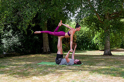 Young man practicing yoga in garden, lying on back balancing woman on feet - p429m2032225 by Image Source
