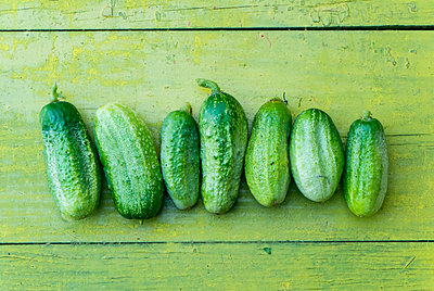 Green cucumbers in a row on wooden table - p555m1231741 by Aleksander Rubtsov