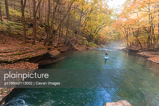 Woman paddle boarding in a fall scene on a clear river - p1166m2113002 by Cavan Images