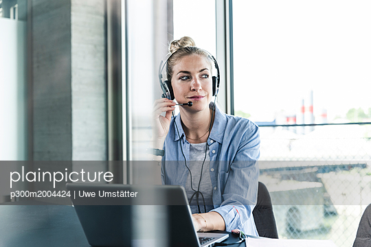 Young businesswoman sitting at desk, making a call, using headset and laptop - p300m2004424 von Uwe Umstätter