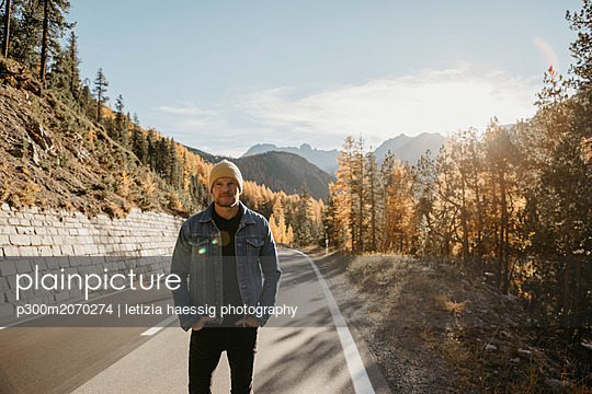 Man travelling through Switzerland, standing on road - p300m2070274 by letizia haessig photography