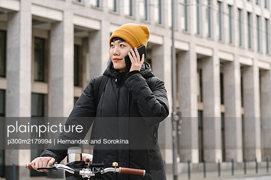 Woman with bicycle on the phone in the city, Frankfurt, Germany - p300m2179994 by Hernandez and Sorokina