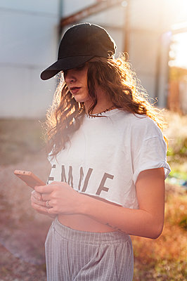 Attractractive millennial woman using smartphone in street at sunset - p1166m2148841 by Cavan Images