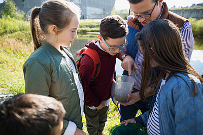 Science teacher and students examining water field trip - p1192m1078412f by Hero Images