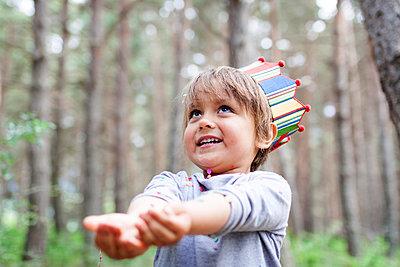 Portrait of smiling little boy wearing paper crown catching confetti - p300m1129958f von Valentina Barreto