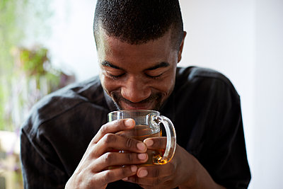 Black man drinking cup of tea - p555m1409879 by Granger Wootz