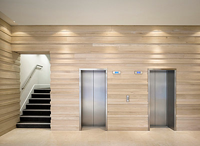 Lifts in lobby of commercial building, King Street, Leeds, Yorkshire. - p855m664653 by Daniel Hopkinson