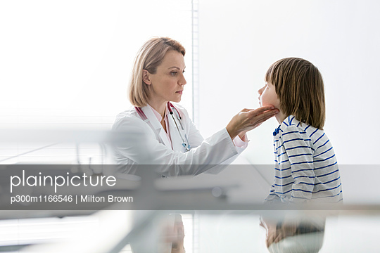 Doctor examining boy in medical practice - p300m1166546 by Milton Brown