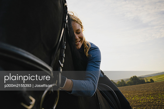 Affectionate woman on horse on a field in the countryside - p300m2155393 von Joseffson