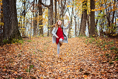 Young Red Hair Girl Playing Outside in Fall Leaves - p1166m2147076 by Cavan Images