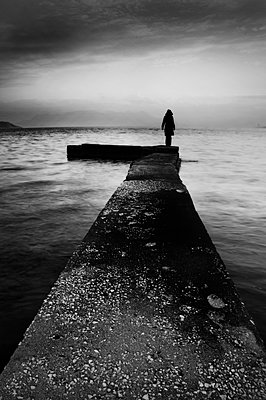 Woman stands on pier by the sea at twilight - p1445m2157981 by Eugenia Kyriakopoulou