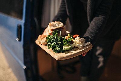 Frau hält Schneidebrett mit vegetarischen Lebensmitteln aus Campervan - p1497m2071430 von Sascha Jacoby