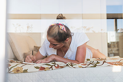 Young woman lying on bed at home writing in diary - p300m2029740 by Kike Arnaiz