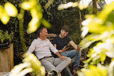 Father and son talking while sitting on bench in backyard - p300m2276919 by Gustafsson