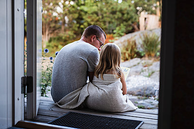 Father and daughter sitting at doorstep - p312m2139637 by Anna Johnsson