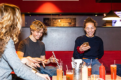 Cheerful multi-ethnic teenage friends enjoying while sitting on sofa at restaurant - p426m1588377 by Maskot