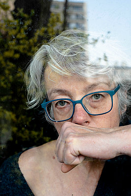 Grey-haired woman looking out of window - p445m2173640 by Marie Docher
