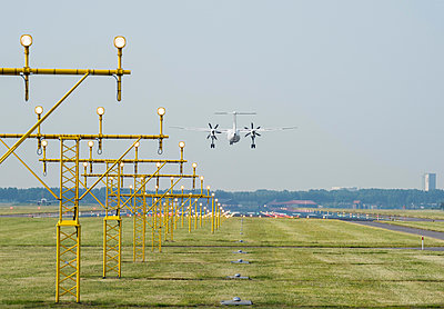 Airplane landing by runway landing lights, Schiphol, North Holland, Netherlands, Europe - p924m1480436 by Mischa Keijser