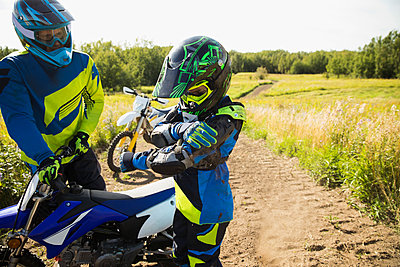 Father helping daughter with motorbike on sunny rural dirt road - p1192m1500153 by Hero Images