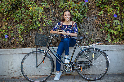 Portrait of smiling teenage girl with cell phone and bicycle - p300m2005262 von zerocreatives