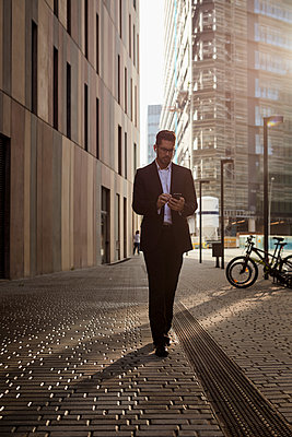 Businessman walking in the city checking cell phone - p300m2070070 by Mauro Grigollo