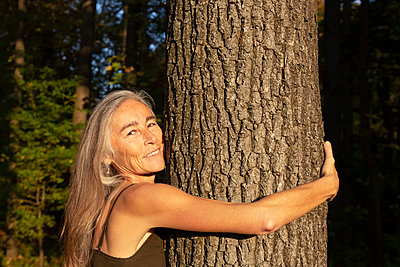 Smiling woman with long gray hair hugging tree at park - p300m2240424 by Christina Falkenberg
