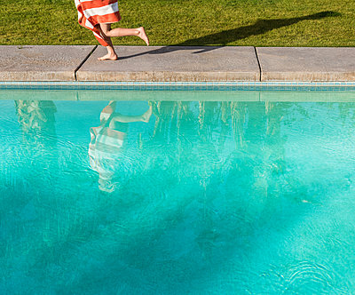 Waist down view of boy wrapped in towel running on poolside - p924m1468933 by JLPH