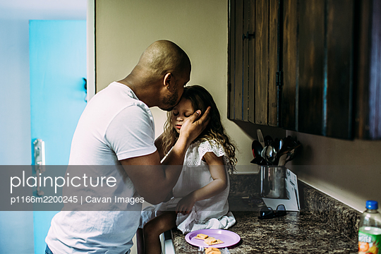 Dad kissing daughter while she sits on kitchen counter - p1166m2200245 by Cavan Images