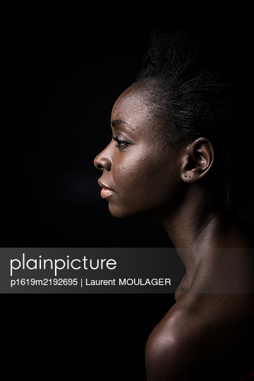 Profile portrait of a young black girl over with a black background - p1619m2192695 by Laurent MOULAGER