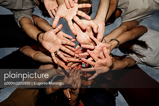 Group of friends stacking hands against sky in park at sunset - p300m2202930 by Eugenio Marongiu