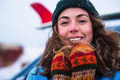 Woman surfer portrait with frozen surfboard - p1166m2177075 by Cavan Images
