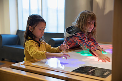 Boy and girl playing with touch screen light display in science center - p1192m1194211 by Hero Images
