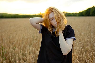 Frau mit blonden Haaren in einem Kornfeld - p1646m2229943 von Slava Chistyakov