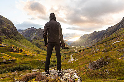 UK, Scotland, Man looking at view with the Three Sisters of Glencoe mountains on the left and the A82 road in the middle of the valley - p300m2081396 by William Perugini