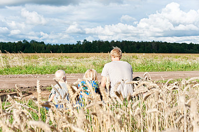 Father with children sitting near field - p312m1442912 by Rebecca Wallin