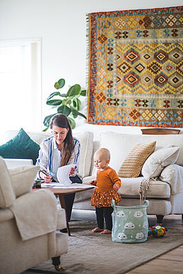 Female professional freelancing while daughter looking at papers on table in living room - p426m2117043 by Maskot