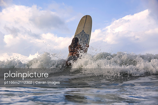 Female surfer on a wave - p1166m2112302 by Cavan Images