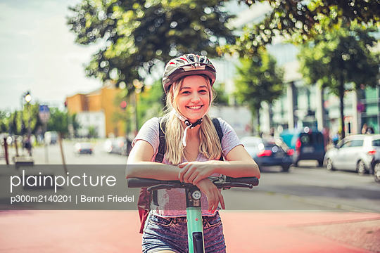 Portrait of relaxed young woman with cycling helmet leaning on handlebar of E-Scooter, Berlin, Germany - p300m2140201 by Bernd Friedel