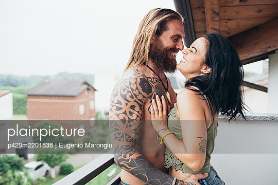 Bearded tattooed man with long brunette hair and woman with long brown hair standing on a balcony, hugging and kissing.  - p429m2201838 by Eugenio Marongiu