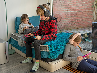 Three children reading or listening to music at home - p1132m2176559 by Mischa Keijser