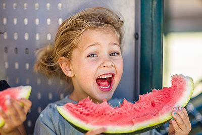 Portrait of happy girl eating a watermelon in kindergarten - p300m2104337 by zerocreatives