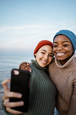 Young women wearing knit hat taking selfie on mobile phone while standing against sky - p300m2243456 by Rafa Cortés