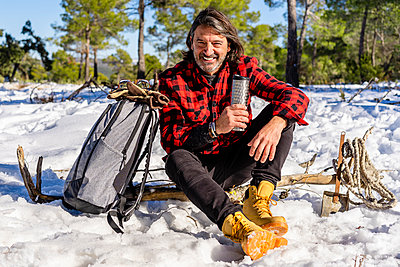 Mature man resting while sitting with backpack on snow in forest - p300m2250957 by Javier De La Torre Sebastian