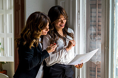 Smiling female entrepreneurs discussing over strategy near window at office - p300m2264499 by VITTA GALLERY
